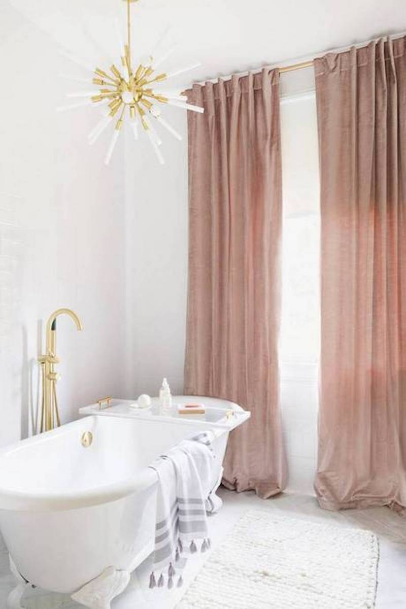 White bathroom with starburst chandelier and pink curtains by Alyssa Rosenheck
