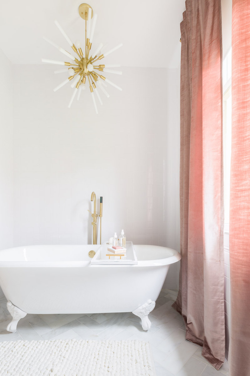 White bathtub with pink curtains by Alyssa Rosenheck