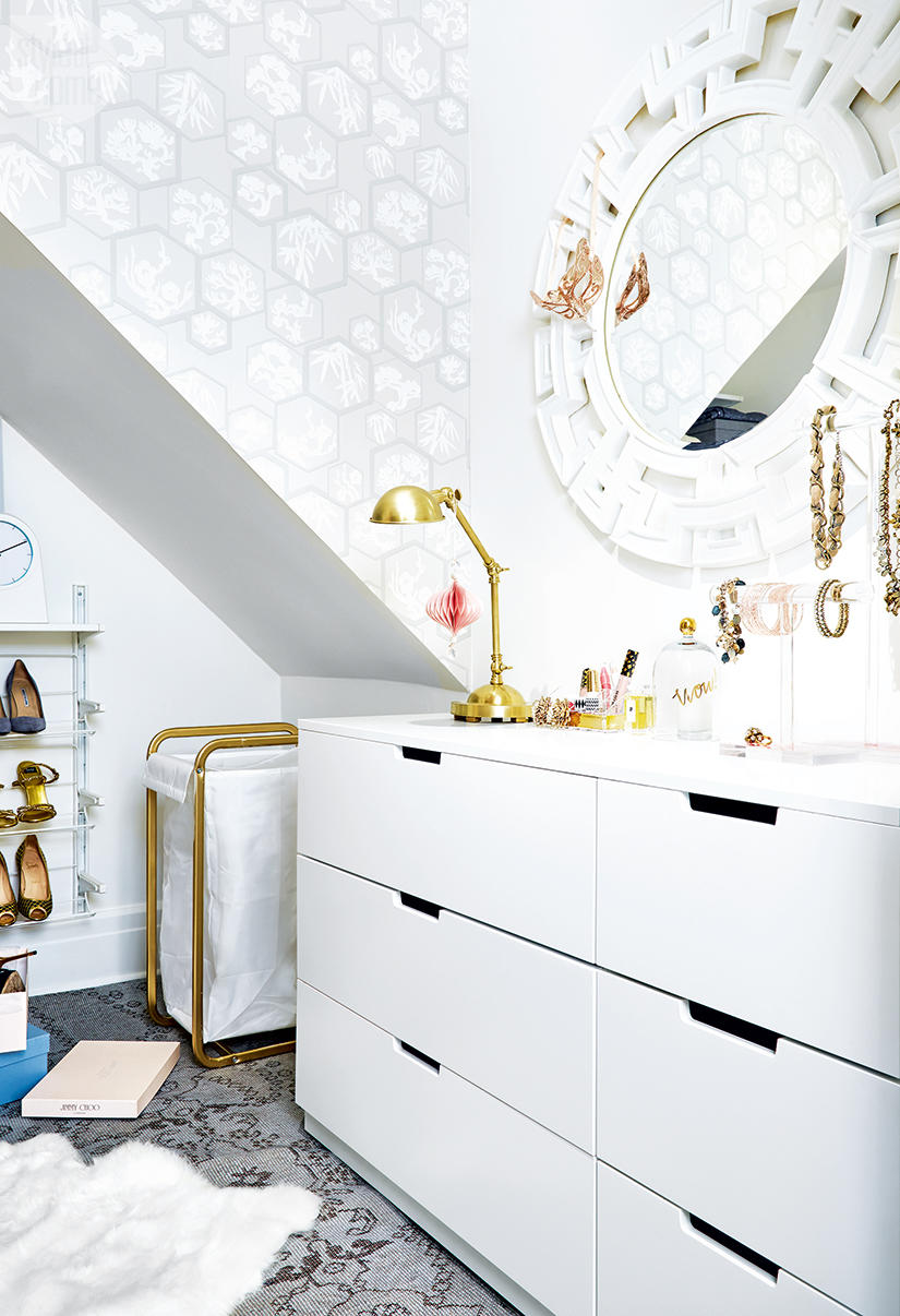 White drawers with a geometric white mirror inside a closet