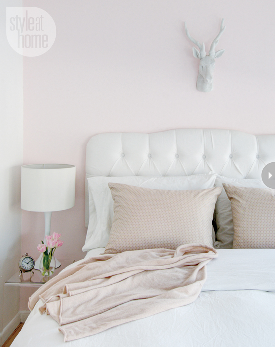 White tufted headboard against blush pink walls in bedroom