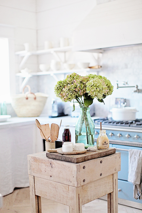 Wooden island with flowers in kitchen
