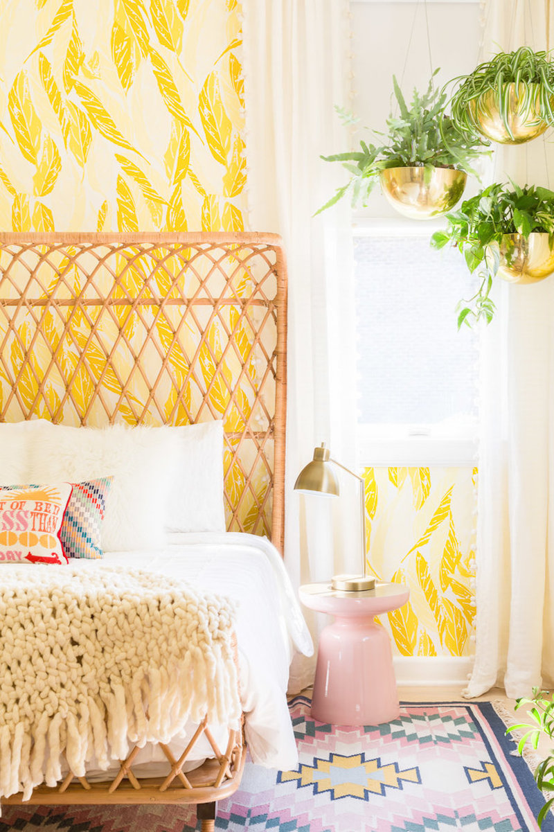 Yellow wallpaper bedroom with wicker headboard by Alyssa Rosenheck