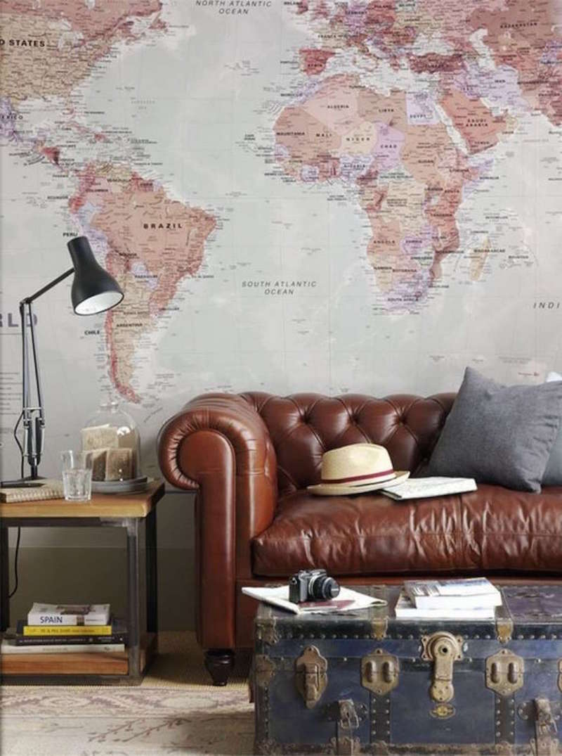 Brown leather couch against wall map mural with vintage trunk