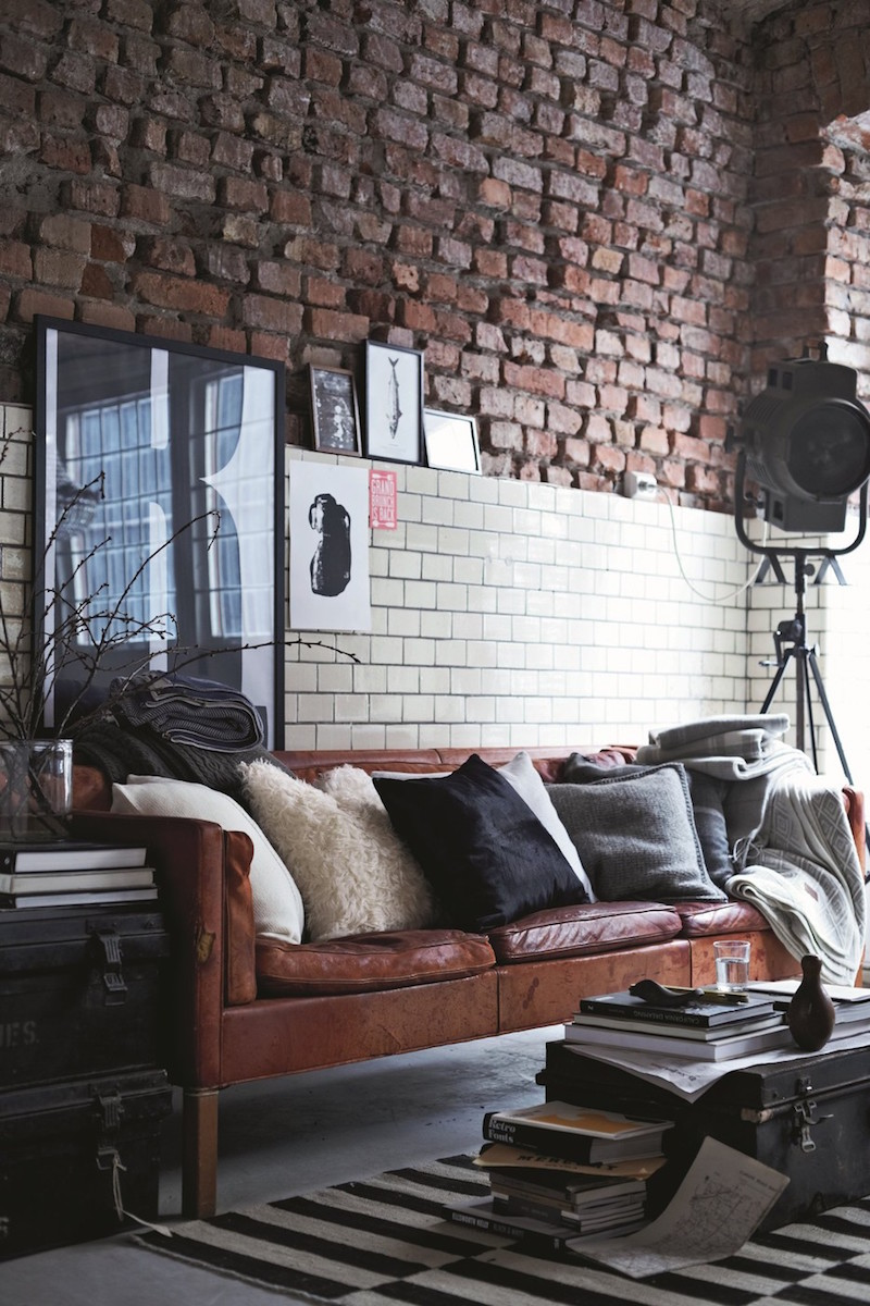 Brown leather sofa against brick wall via Gant