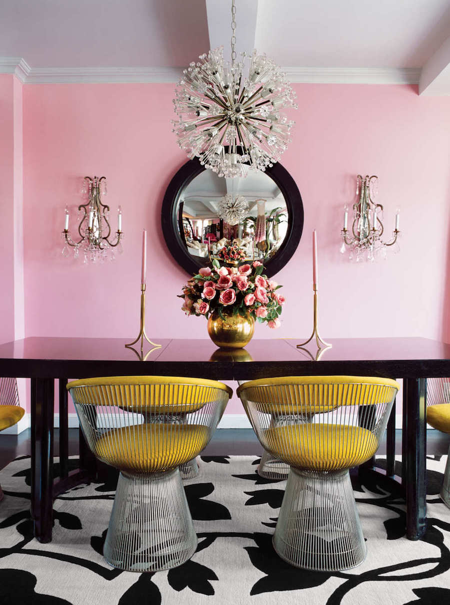 Dining room with pink walls and yellow chairs via elle decoration uk