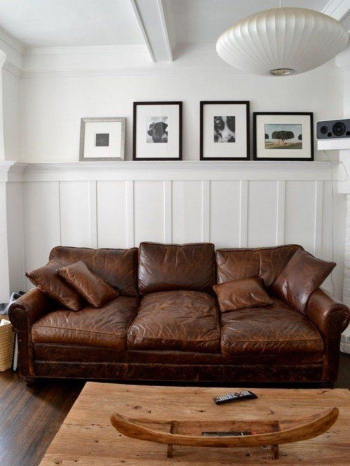 Distressed Brown Leather Couch Against White Wall