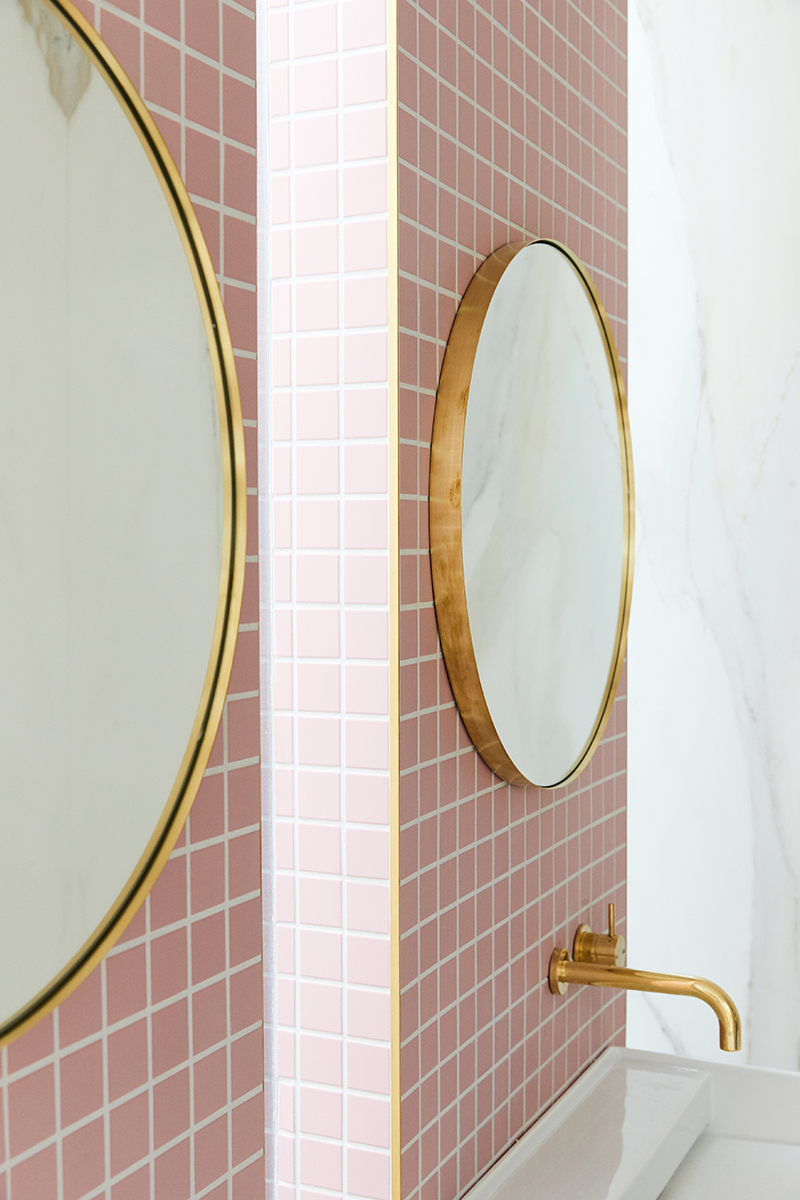 Gold circle mirrors on pink tile bathroom