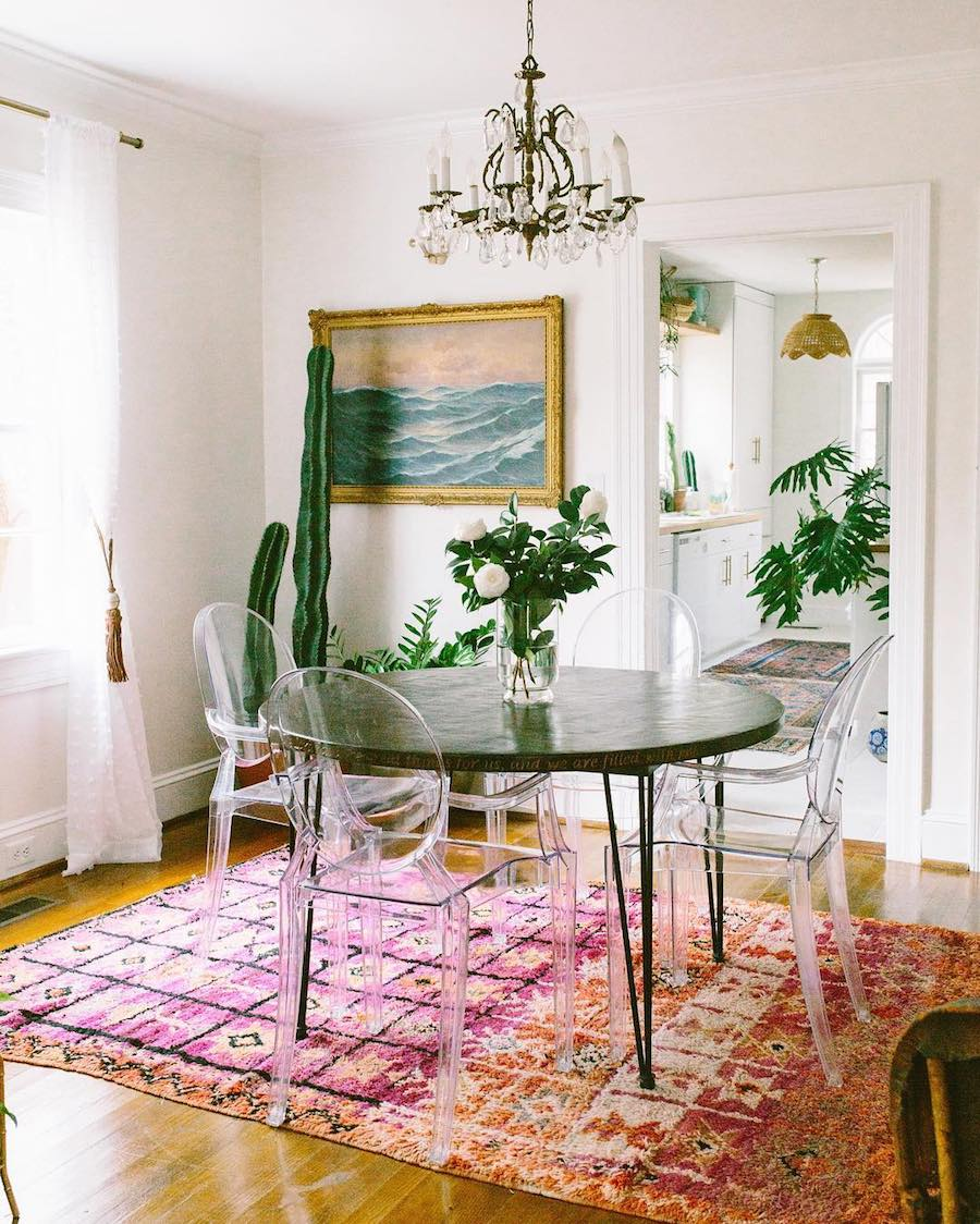 Ghost chairs with dark table and multicolor rug