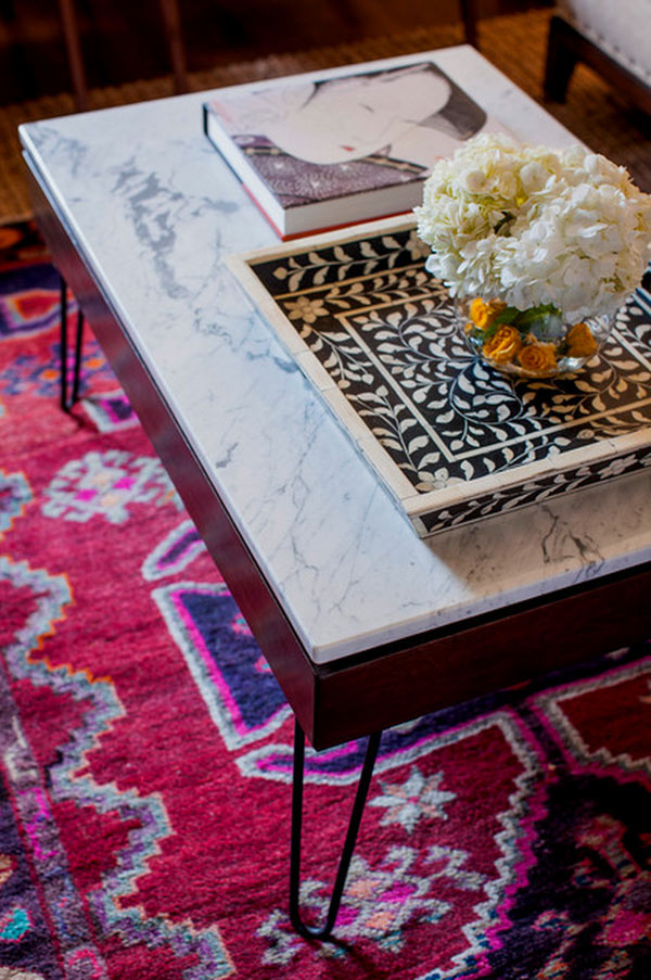 Marble coffee table with red rug via Design Manifest
