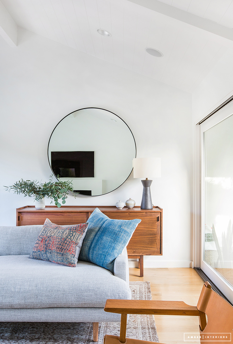 Minimalist Mid-Century living room with round mirror