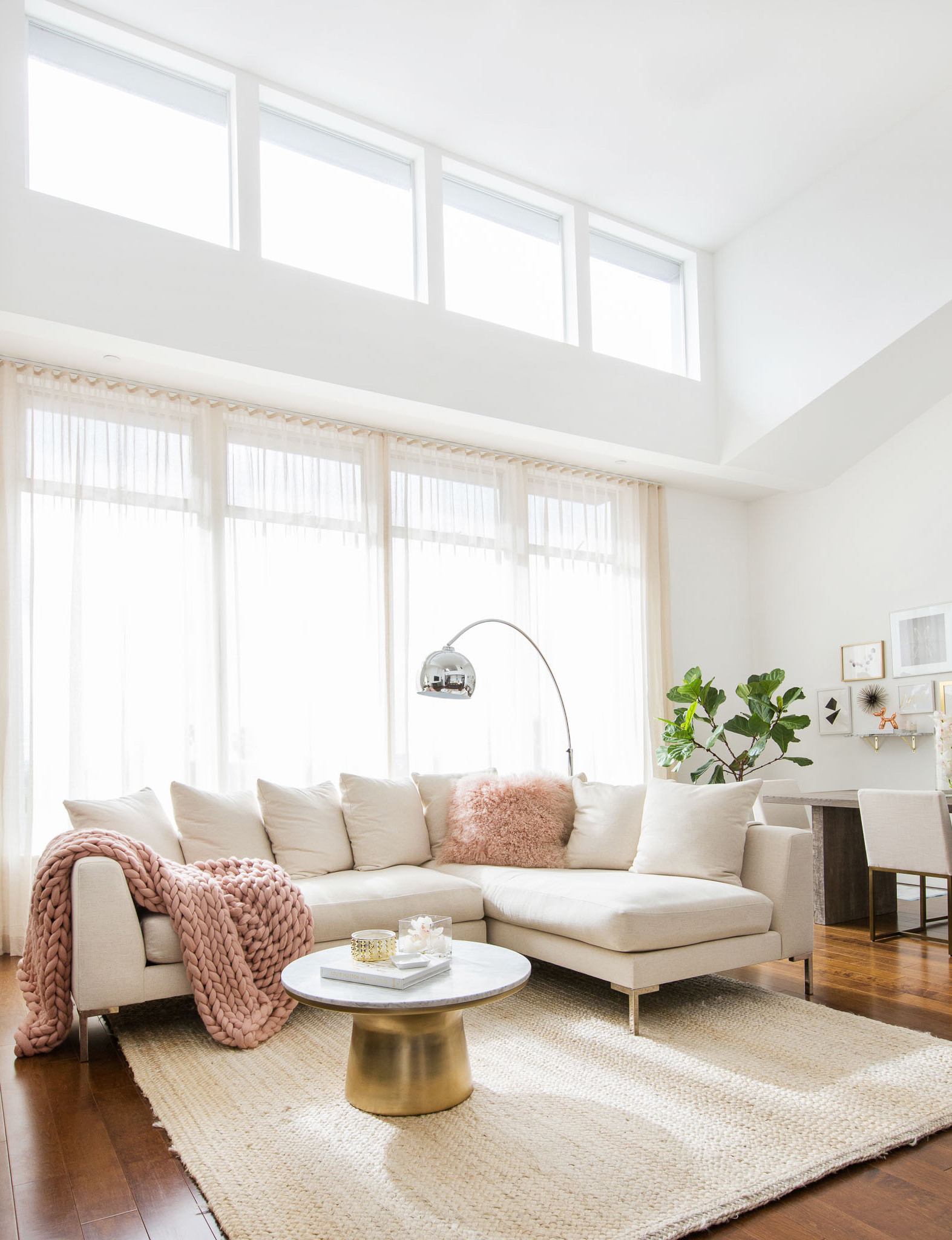 Neutral couch with blush pink throw and pillows with marble table