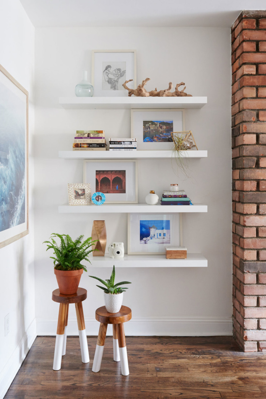 Open white shelving with plants on stools