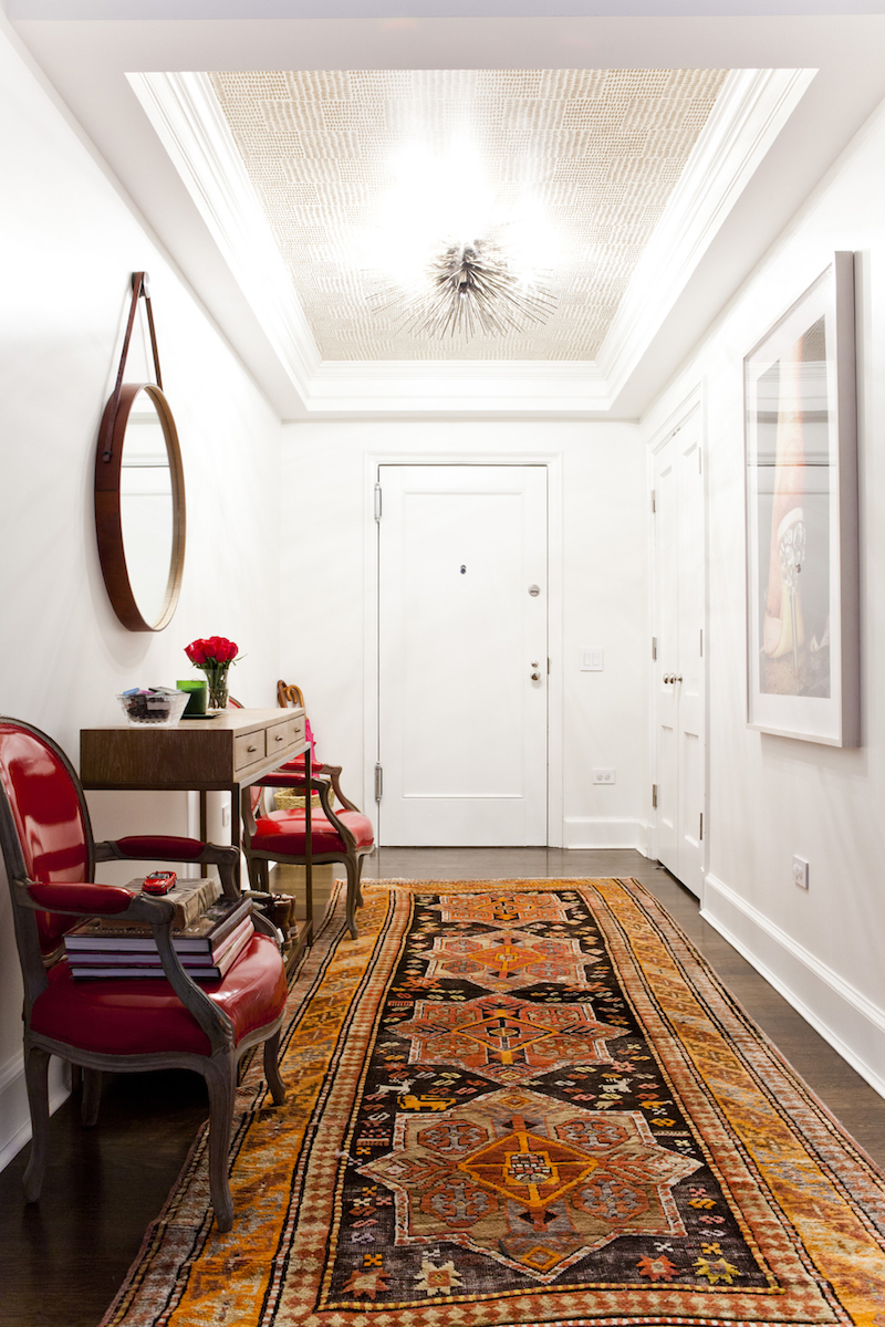 Orange oriental rug entryway via Lilly Bunn