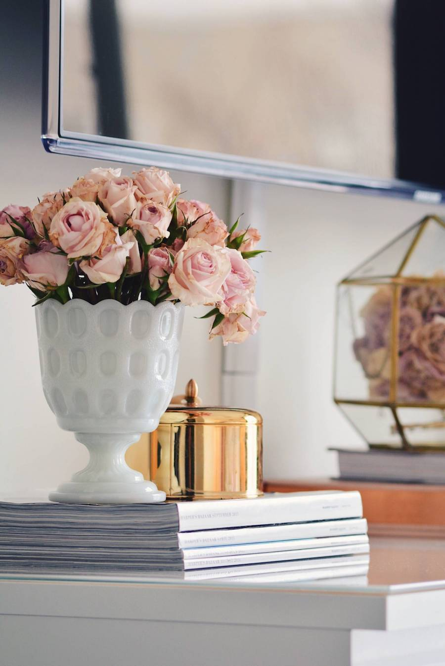 Pink flowers in small white urn on dresser