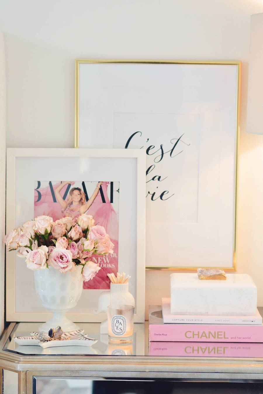 Stacked artwork on mirrored dresser