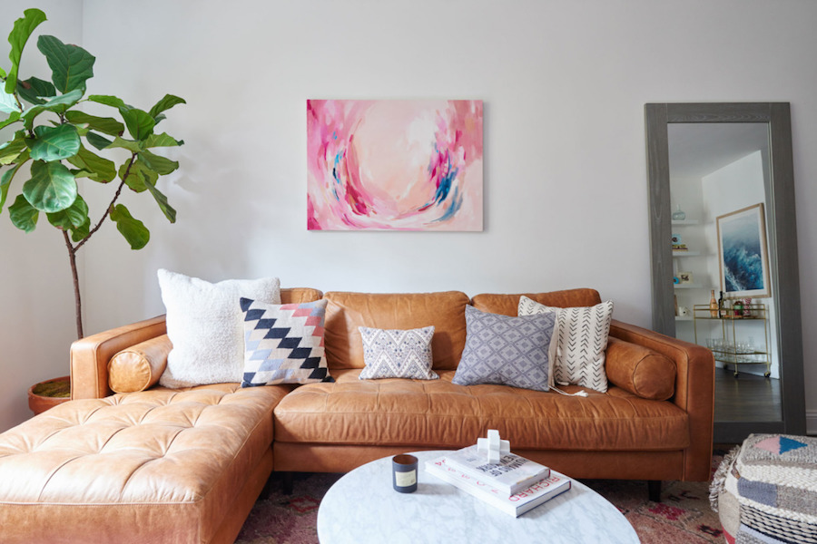 Tan leather couch with pink artwork