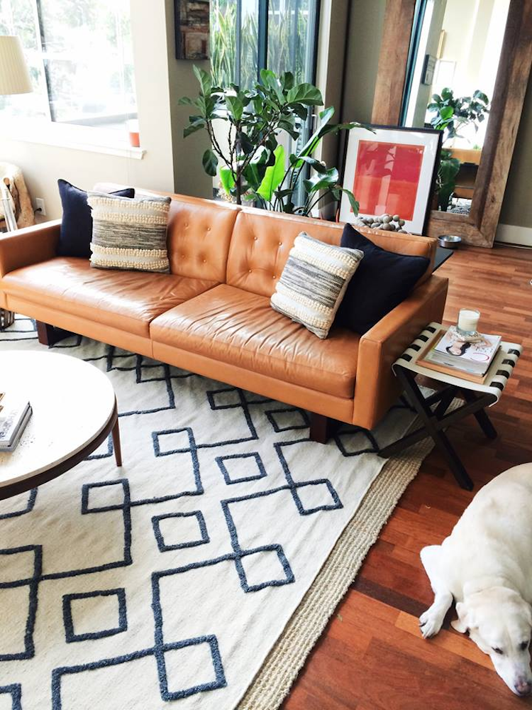Tan leather sofa with geometric rug