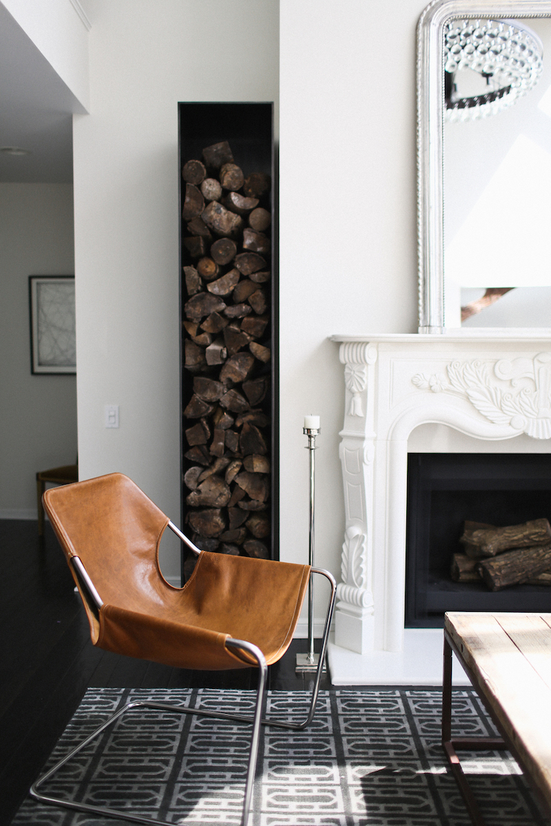 Traditional mantel with firewood and leather chair