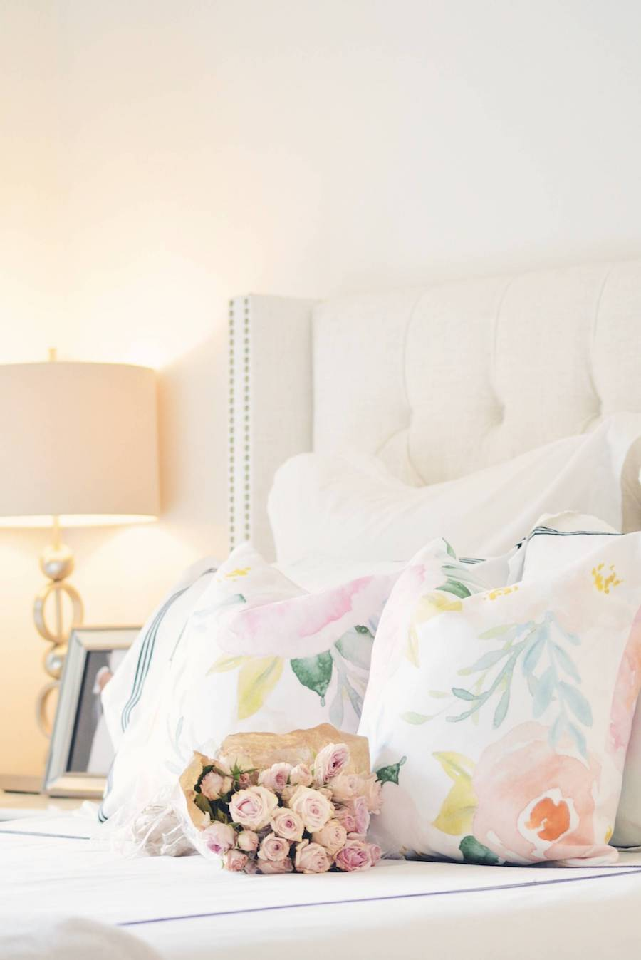 White bed with floral pillows