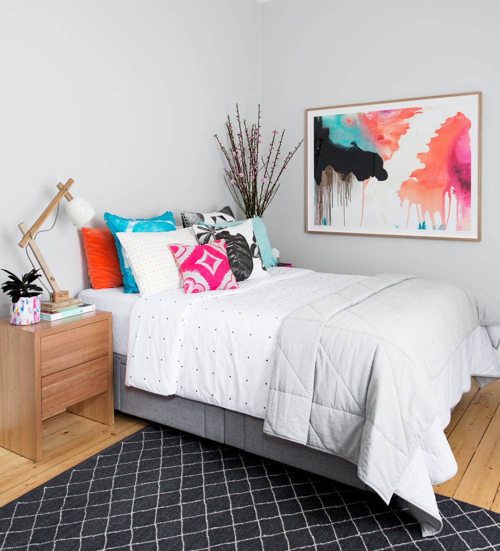 White bedroom with colorful pillows and artwork