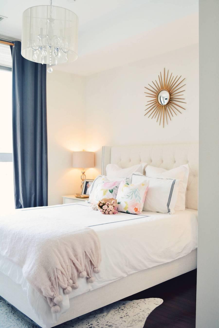 White bedroom with sunburst mirror