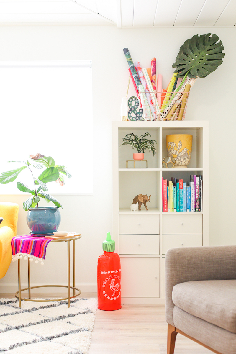 White bookshelves with colorful books and plants