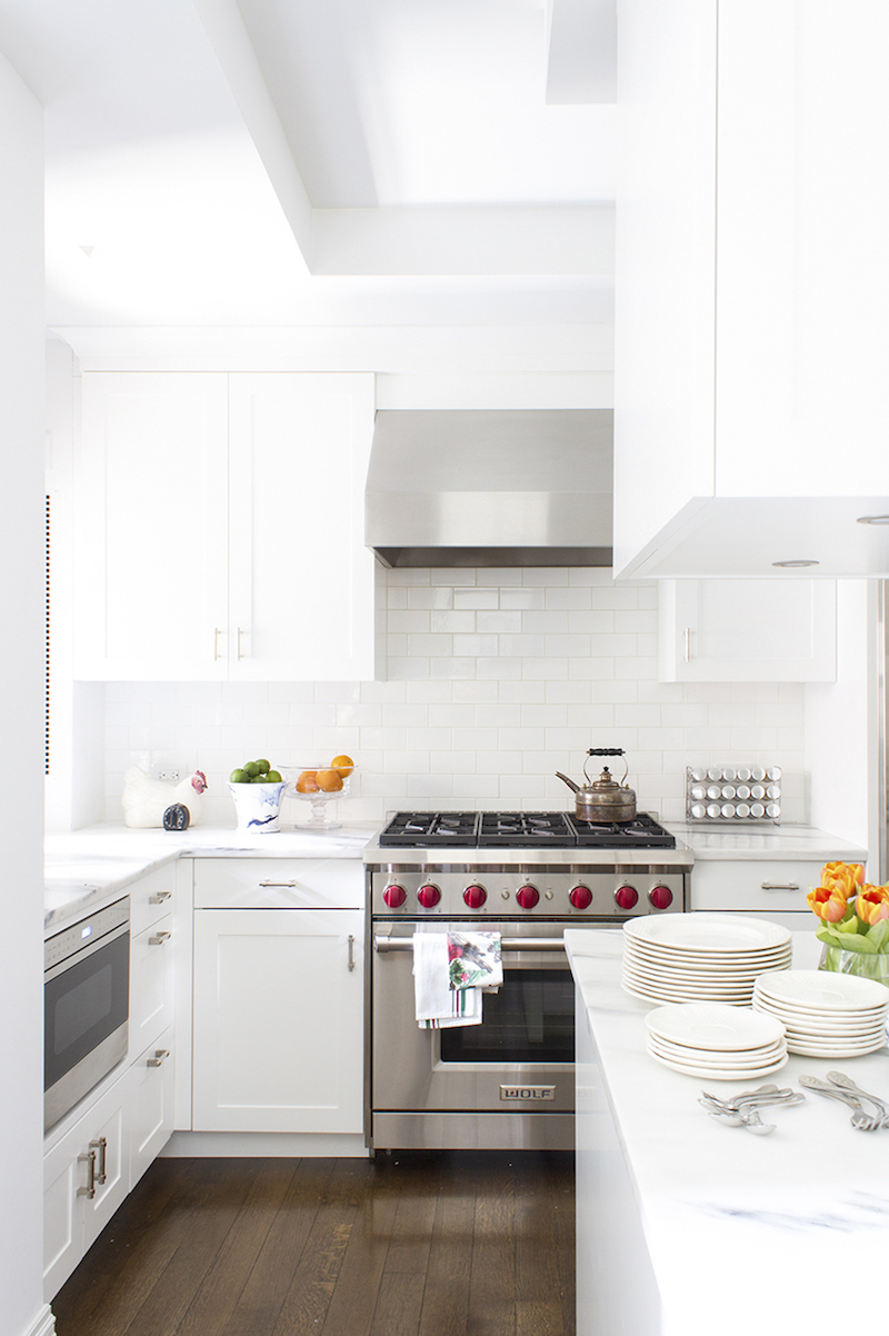 White kitchen with stove with red knobs via Lilly Bunn