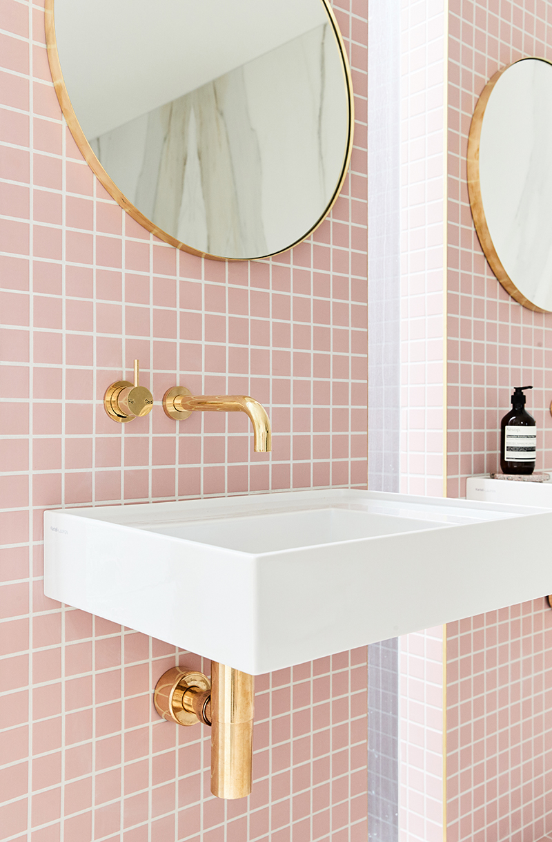 White sink with gold hardware and pink tile