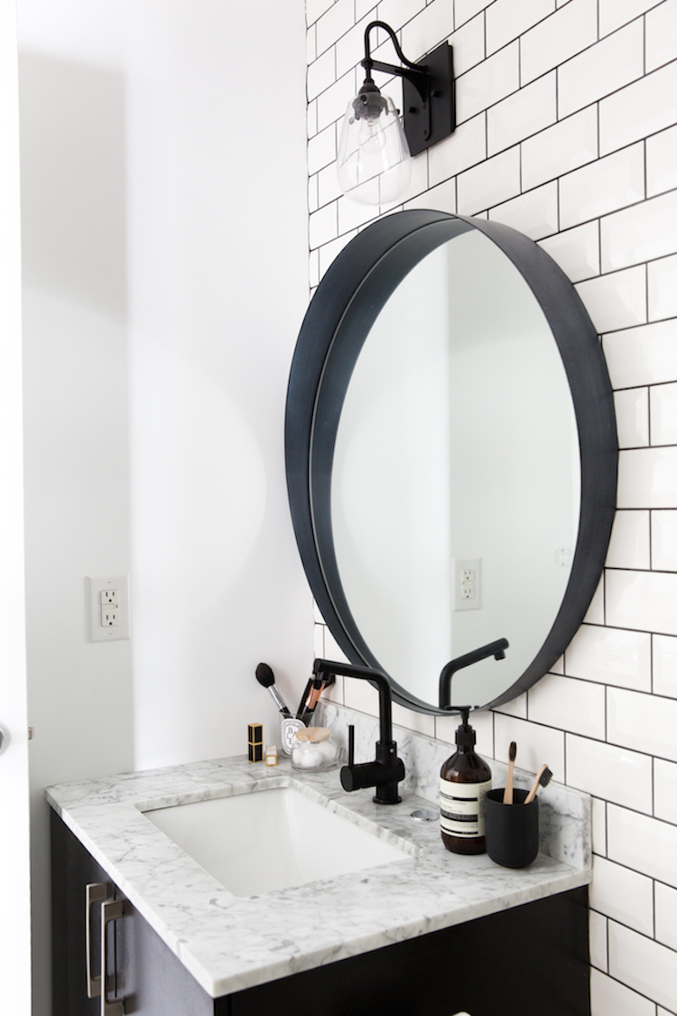 Black oval mirror and marble vanity sink bathroom