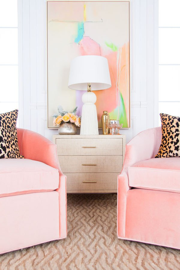 Blush pink sitting chairs with spring art and cheetah pillows