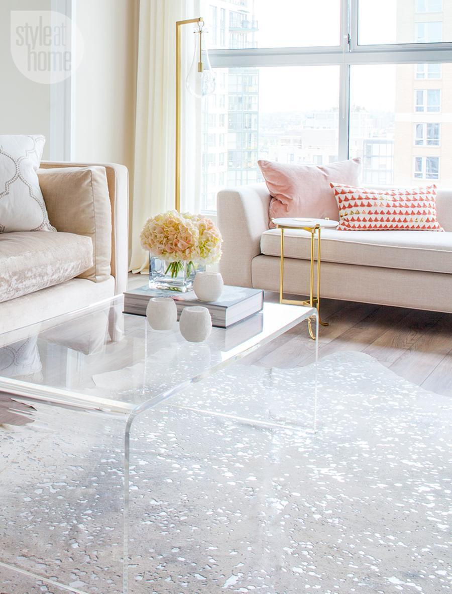 Clear lucite coffee table in neutral couch living room