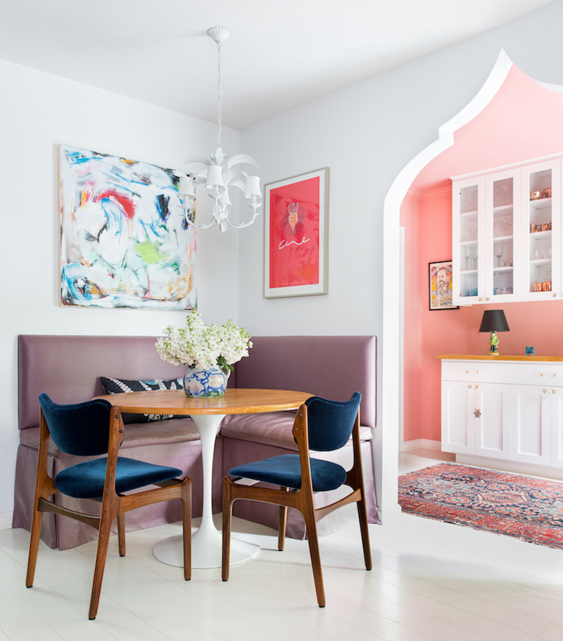 Dining nook with arch and pink wall kitchen