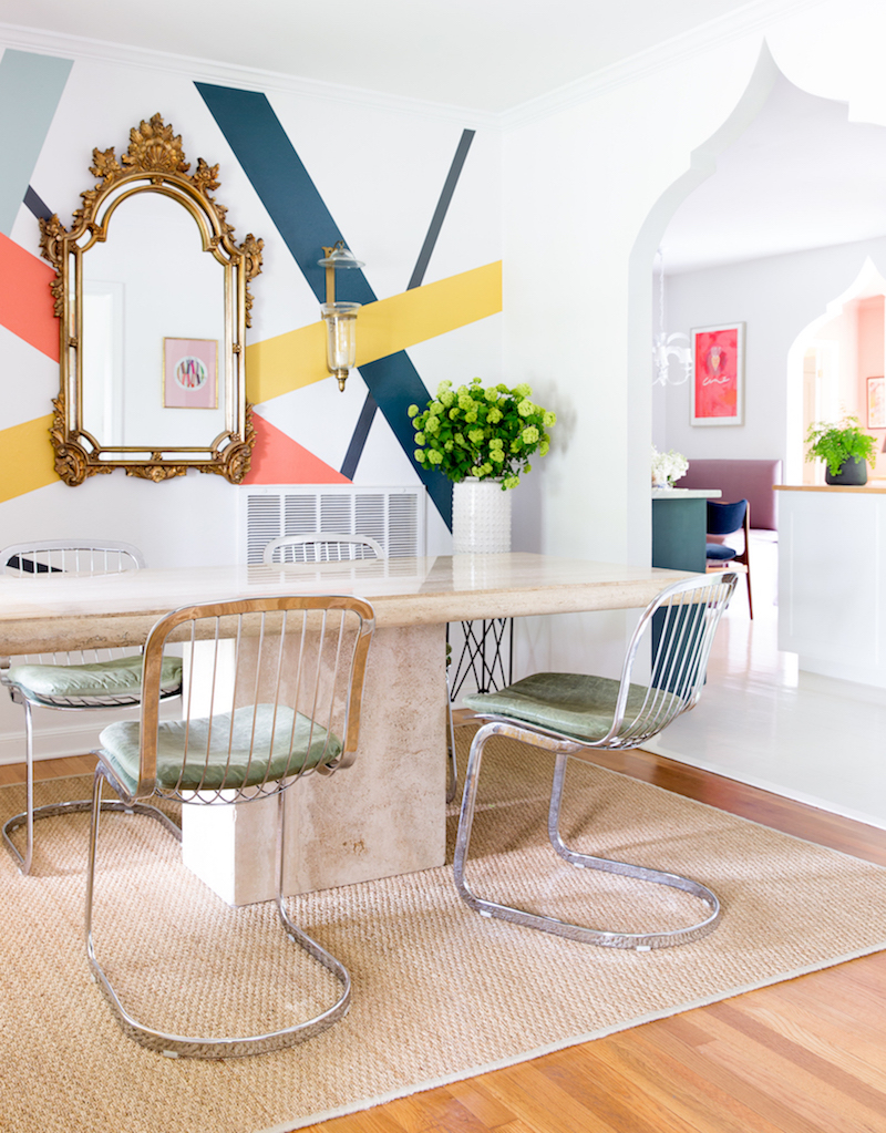 Dining room with gilded mirror and color stripes on wall