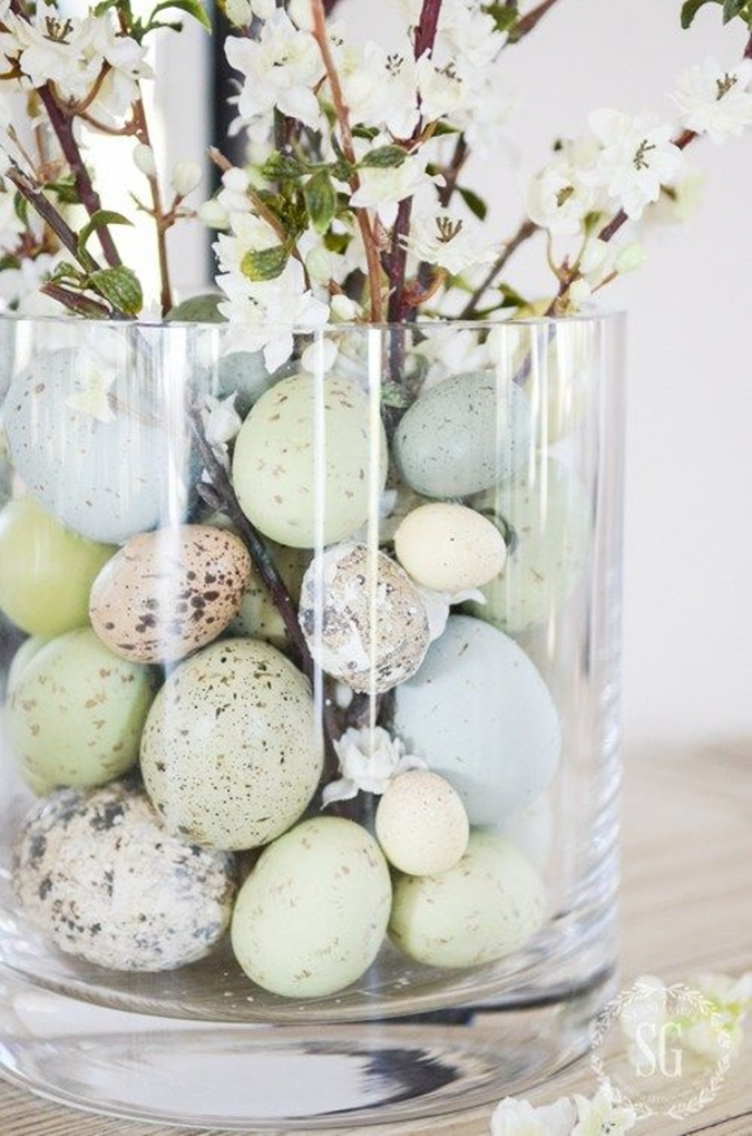 Easter eggs inside clear glass vase of flowers