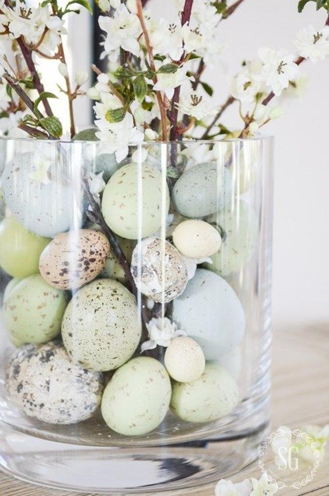 Easter eggs inside clear glass vase of flowers