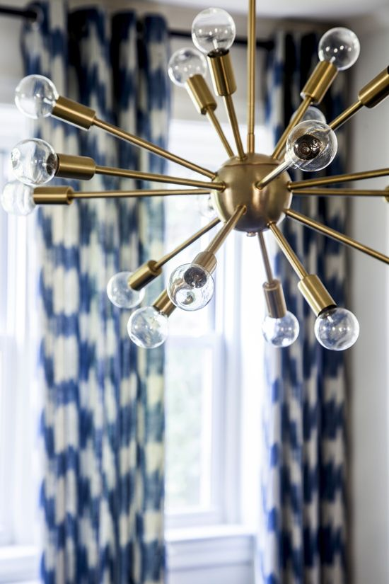 Gold starburst chandelier in front of blue curtains