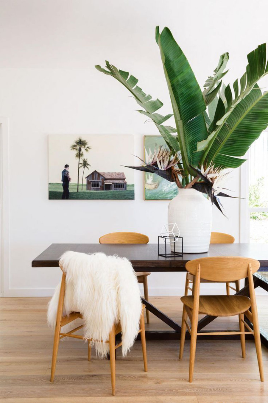 Large palm on dining table with scandinavian chairs