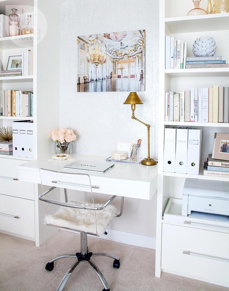 Lucite office chair at white desk with gold lamp