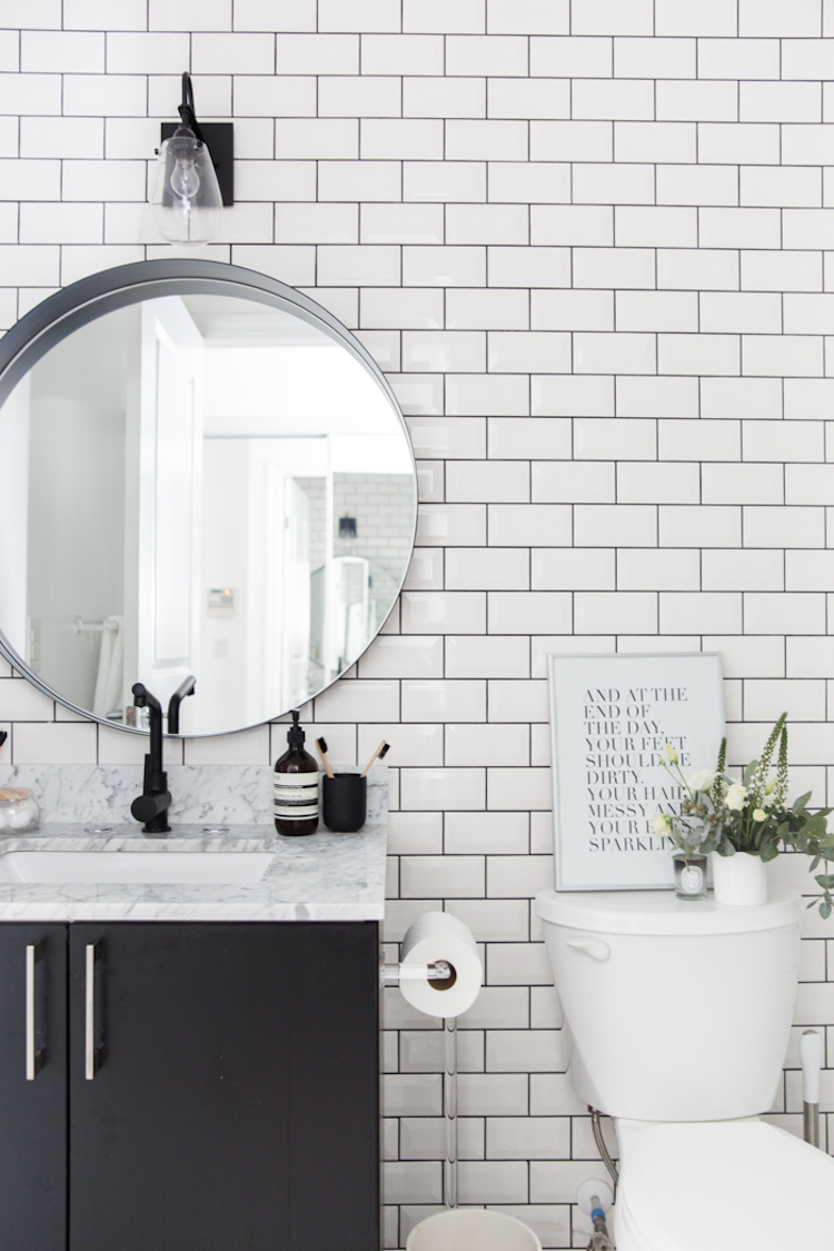 Marble bathroom sink vanity with white tiling and black grout