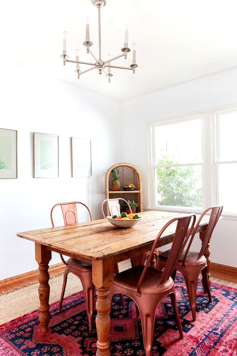 Natural dining table with red oriental rug