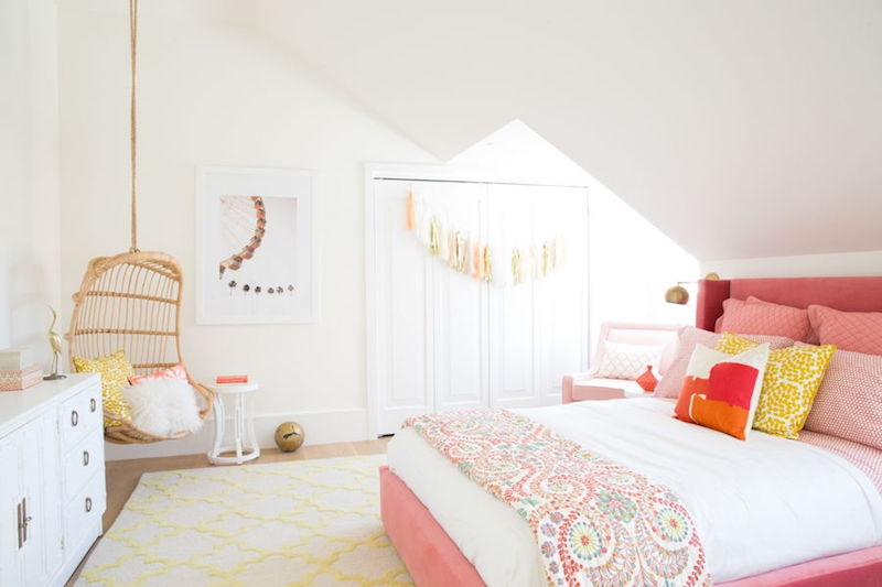 Pink bed with wicker hanging chair in corner