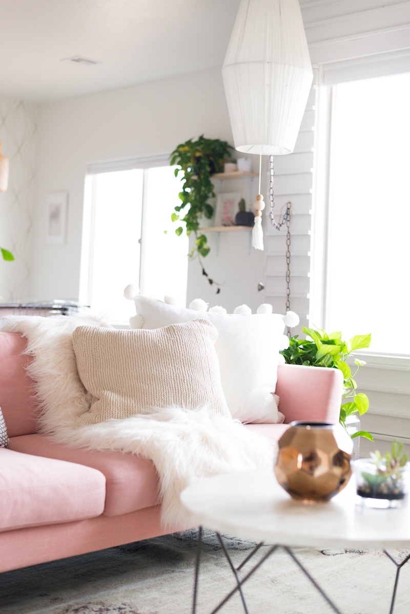 Pink sofa white fur throw and white coffee table