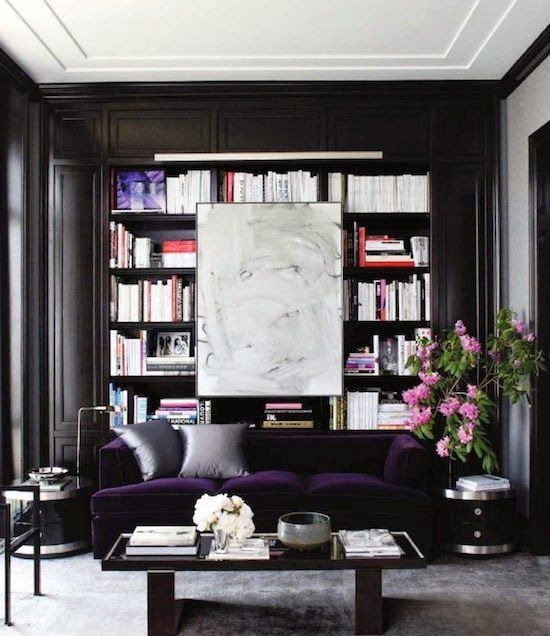Plum velvet sofa with bookcase and white art