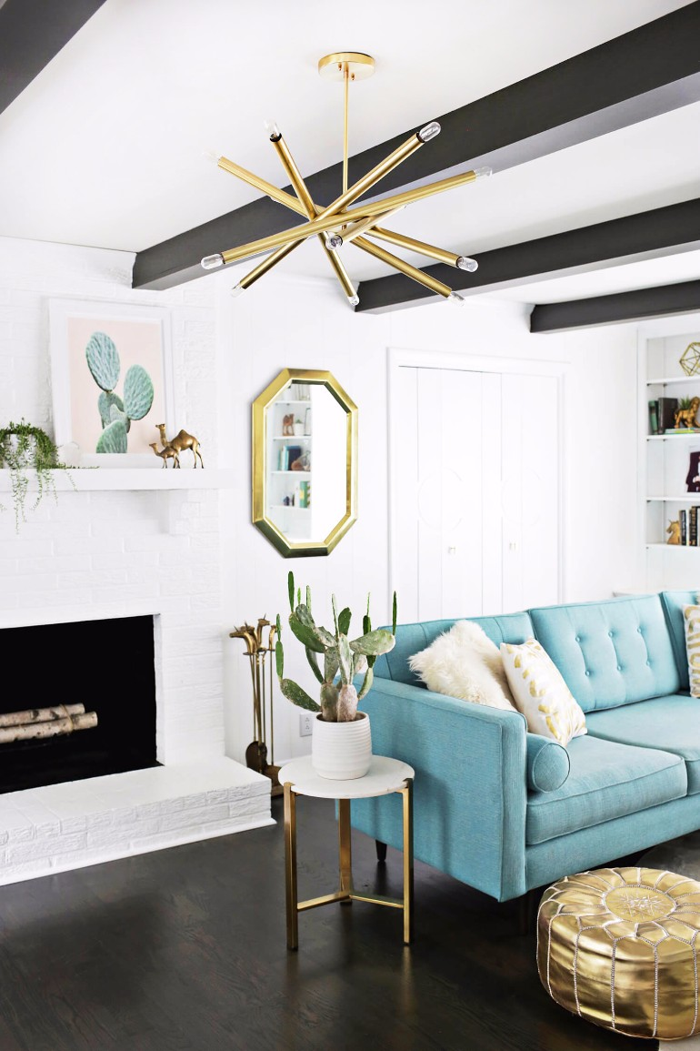 Starburst chandelier in living room with blue sofa via A Beautiful Mess
