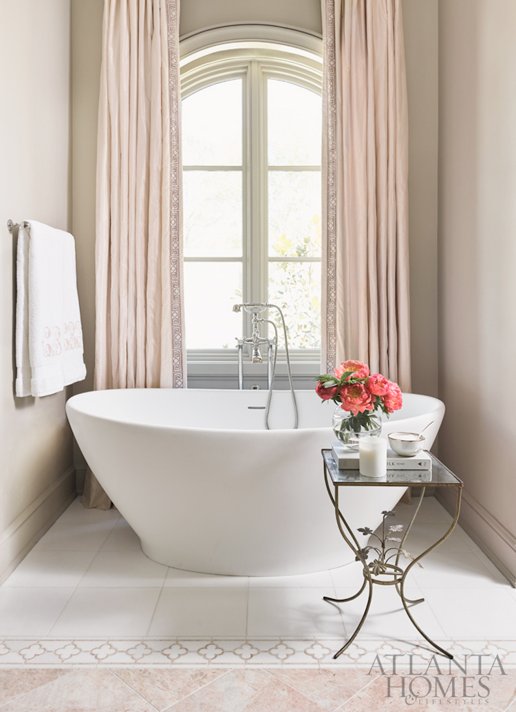 White freestanding bathtub with blush pink curtains