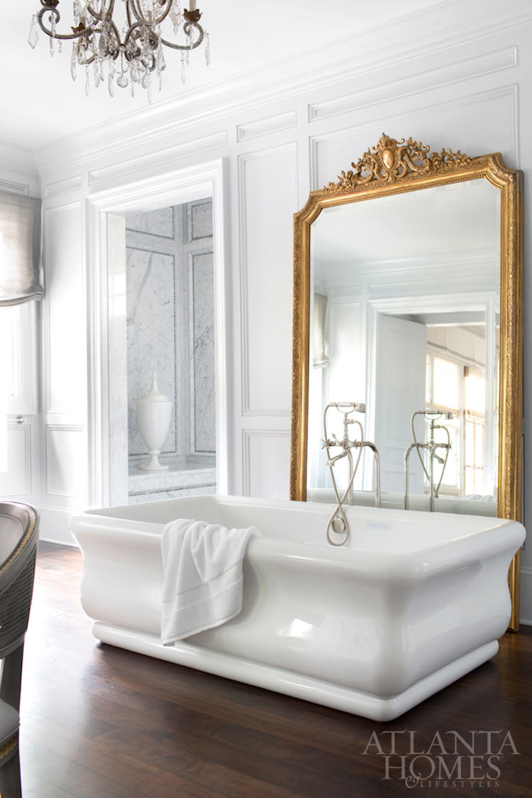 White freestanding tub with gilded mirror behind it