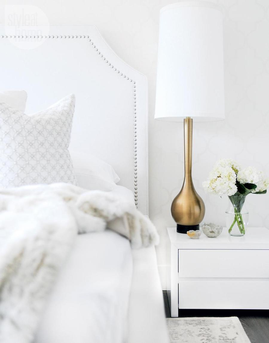 White studded headboard with brass gold table lamp