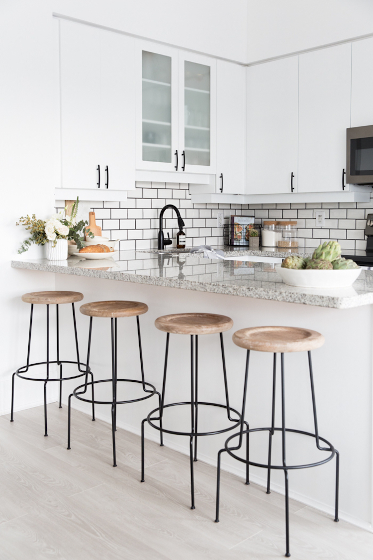 Wooden bar stools near granite kitchen counter