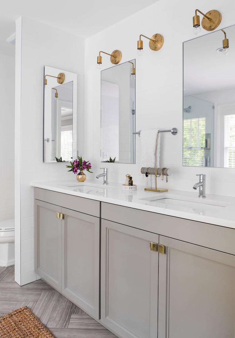 Brass sconces above bathroom vanity