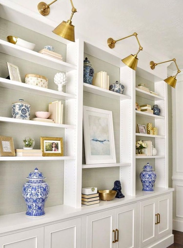 Brass swing arm sconces above bookshelf